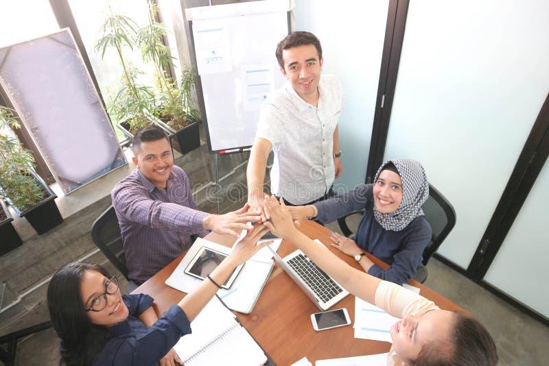 Het commerciële team geven highfive samen bij de bureauvergaderzaal met laptop smartphone en tablet dichtbij vensters met witte r stock foto