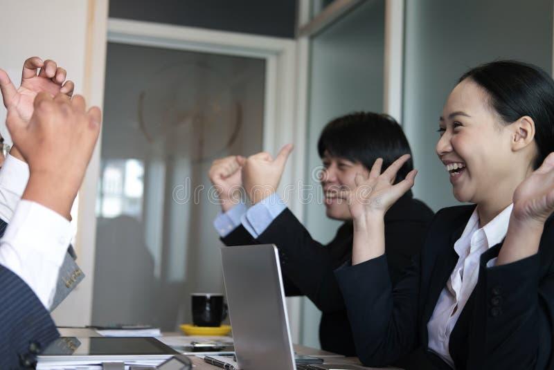 Het commerciële team heft handen met geluk voor succesvol project op vrolijke Aziatische zakenman & onderneemster die vreugde ton stock foto's