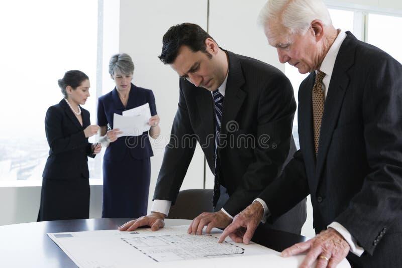 Het commerciële team herzien plannen tijdens vergadering. stock afbeelding