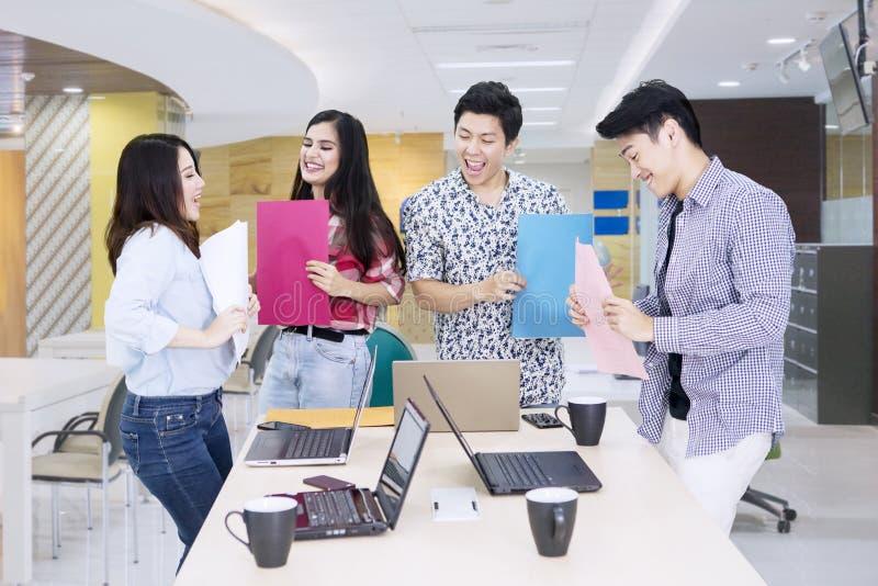 Het commerciële team kijkt gelukkig na het werk in het bureau stock afbeeldingen