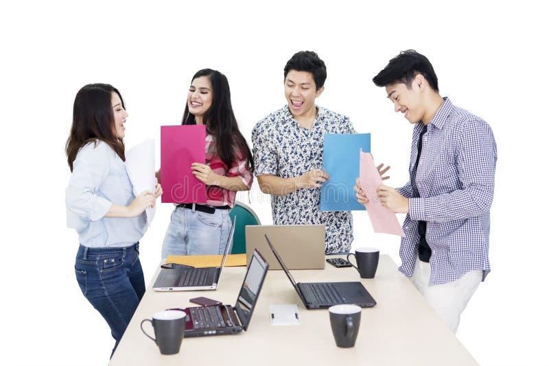 Het commerciële team kijkt gelukkig na het werken aan studio stock fotografie