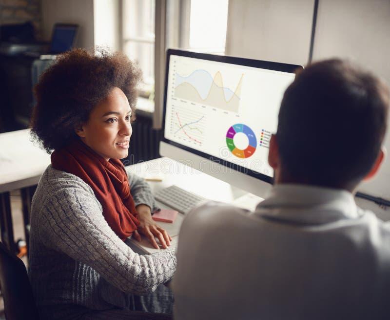 Het commerciële team van twee collega's die aan opiniepeiling werken vloeit samen voort stock afbeelding