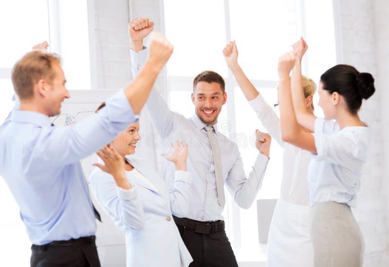 Het commerciële team vieren overwinning in bureau stock fotografie