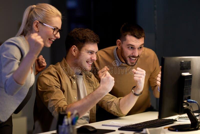 Het commerciële team vieren succes op nachtkantoor stock afbeelding