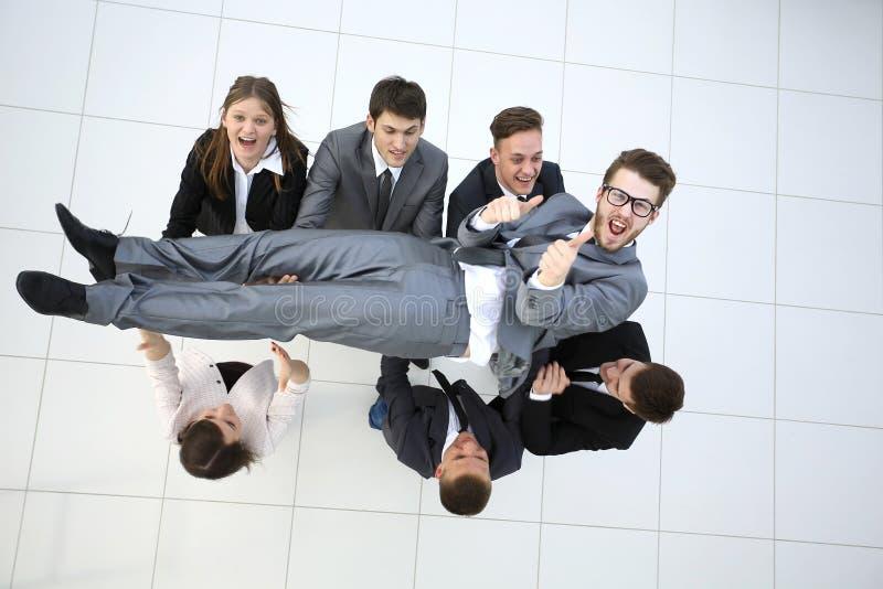 Het commerciële team werpt gelukkig op hun collega in de lucht celeb stock foto
