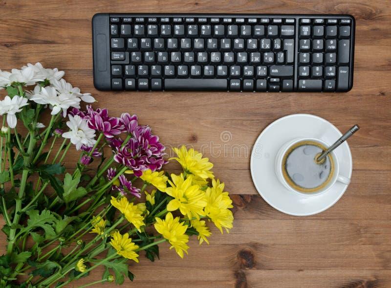 Het computertoetsenbord, de kopkoffie en de bloem onwooden lijst stock foto's