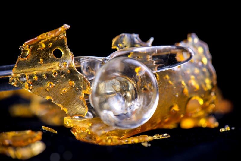 Het concentraataka van de cannabisolie verbrijzelt met geïsoleerde glashulpmiddelen stock foto's