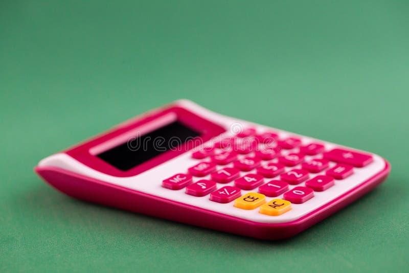 Het concept analyse, analytics, berekeningen De calculator ligt op groene bacground stock fotografie