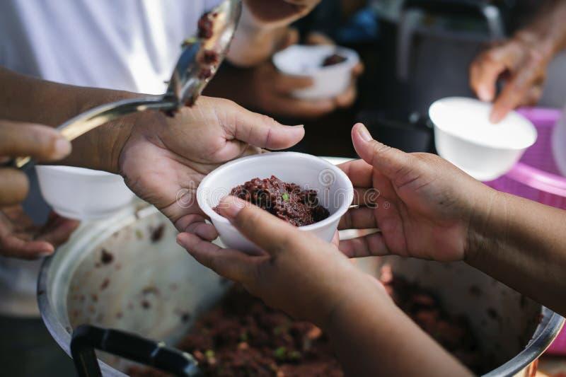 Het concept het bedelaarsprobleem ter wereld: De Hand van de Bedelaars ontvangt liefdadigheidsvoedsel van mede menselijke wezens: stock foto
