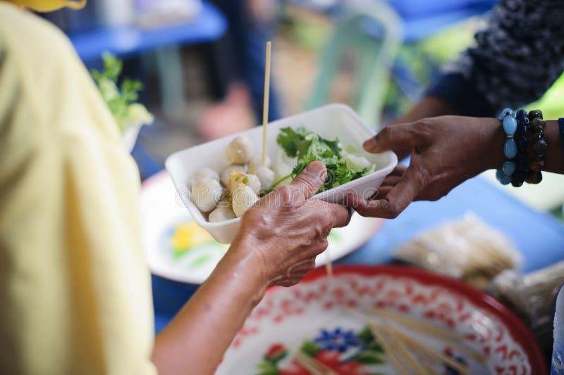 Het concept het bedelaarsprobleem ter wereld: De Hand van de Bedelaars ontvangt liefdadigheidsvoedsel van mede menselijke wezens: royalty-vrije stock afbeeldingen
