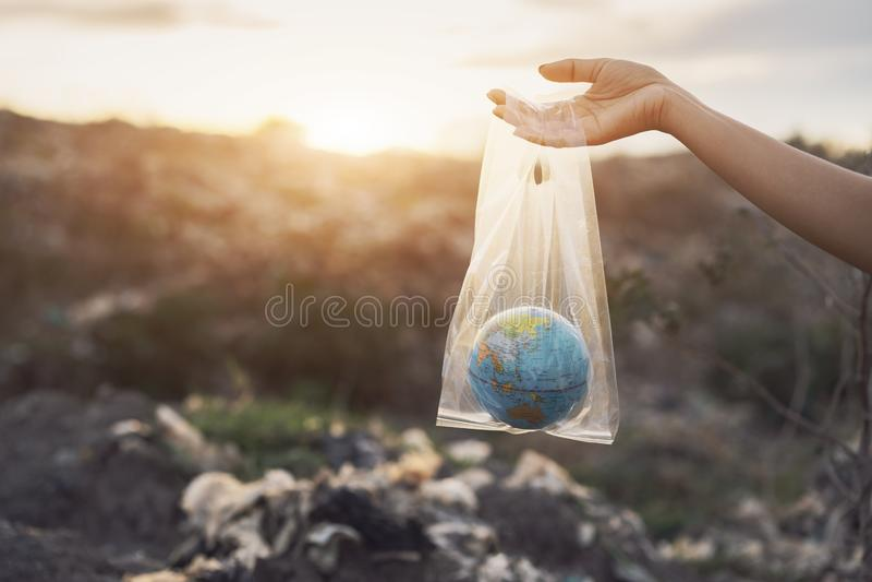 Het concept de Dag van het Wereldmilieu De vrouwenhand houdt de aarde in een plastic zak op huisvuilstapel in van de afvalstortpl stock foto's