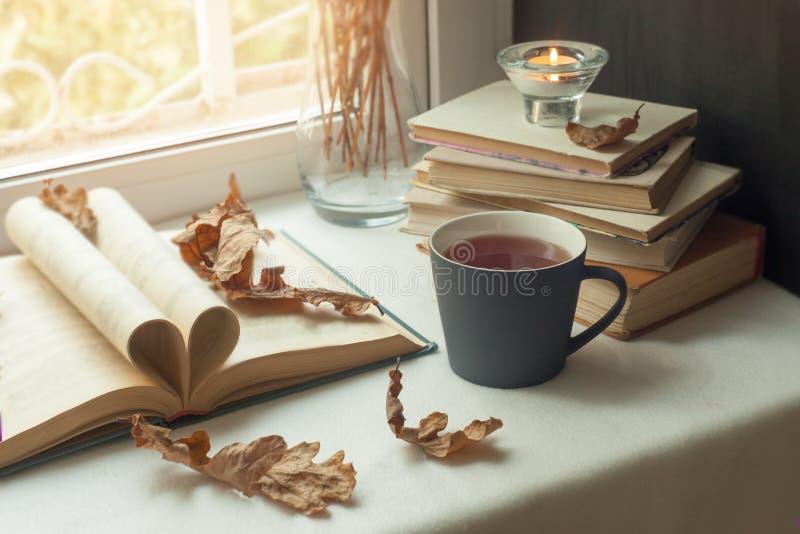 Het concept de tijd van de de herfstlezing en romantische, Warme, comfortabele vensterzetel opende boek, licht door blinden, het  stock afbeeldingen