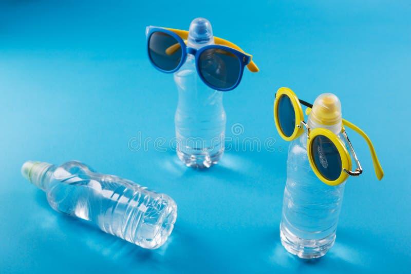 Het concept de zomer en de rust, drie plastic flessen water, liggen, flessen zonglazen, zijn de flessen als mensen, a stock afbeelding