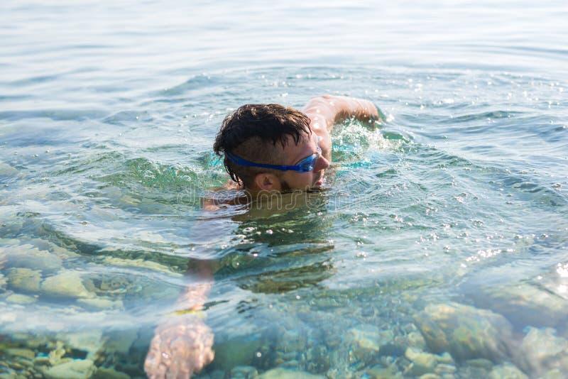 Het concept een actieve levensstijl: een mens zwemt in zwemmende beschermende brillen royalty-vrije stock afbeelding