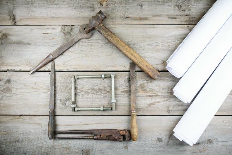 Het concept een huis in aanbouw Oude houten Desktop Oude roestige timmerwerkhulpmiddelen stock afbeeldingen