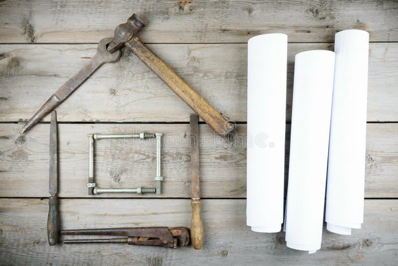 Het concept een huis in aanbouw Oude houten Desktop Oude roestige timmerwerkhulpmiddelen stock foto