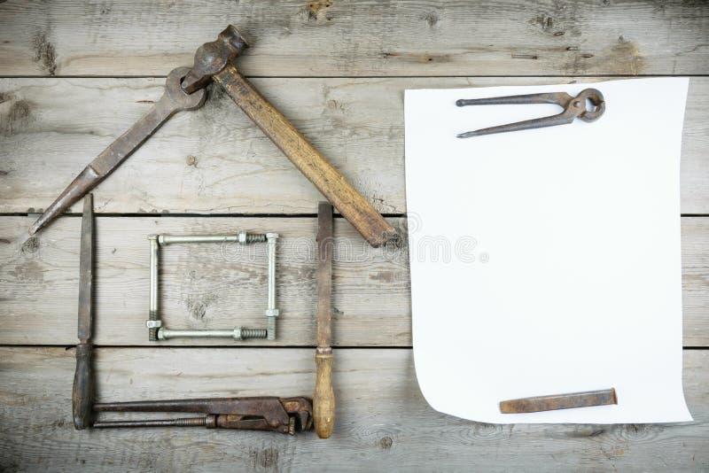 Het concept een huis in aanbouw Oude houten Desktop Oude roestige timmerwerkhulpmiddelen Verticaal model royalty-vrije stock fotografie