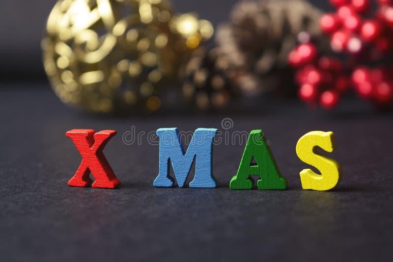 Het concept een Nieuw jaar, Kerstmis Het woord van multicolored brieven op houten Kerstmisachtergrond met giften, denneappels, Ch stock foto