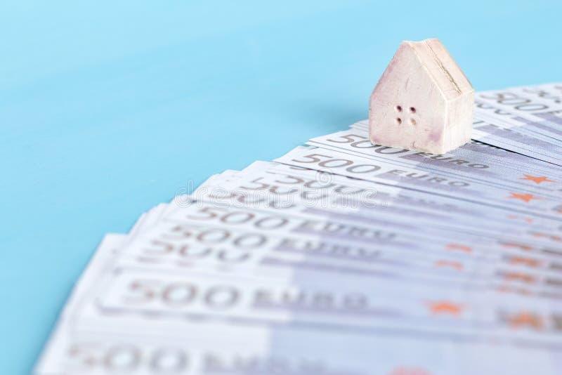 Het concept een stuk speelgoed huis op een achtergrond van bankbiljetten van 500 euro royalty-vrije stock afbeelding