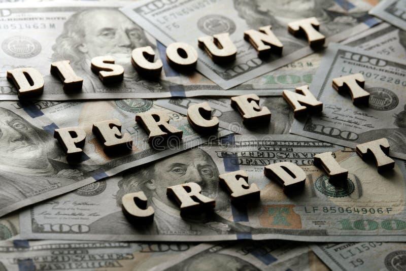 Het concept financiële transacties en bankleningen De KORTING, PERCENTEN, KREDIET wordt opgemaakt van houten brieven op de achter stock fotografie