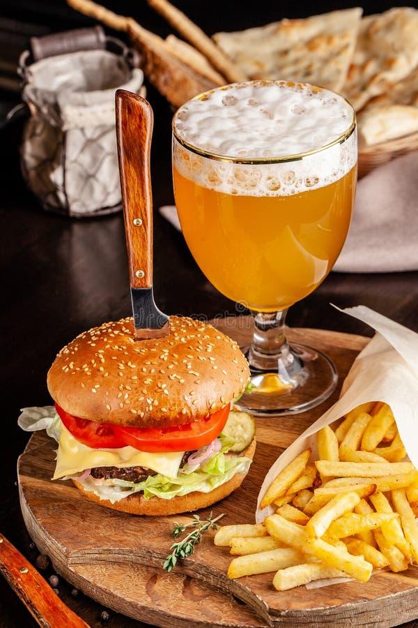 Het concept Italiaanse keuken Italiaanse hamburger met frieten op een houten raad en een glas licht bier met schuim stock foto