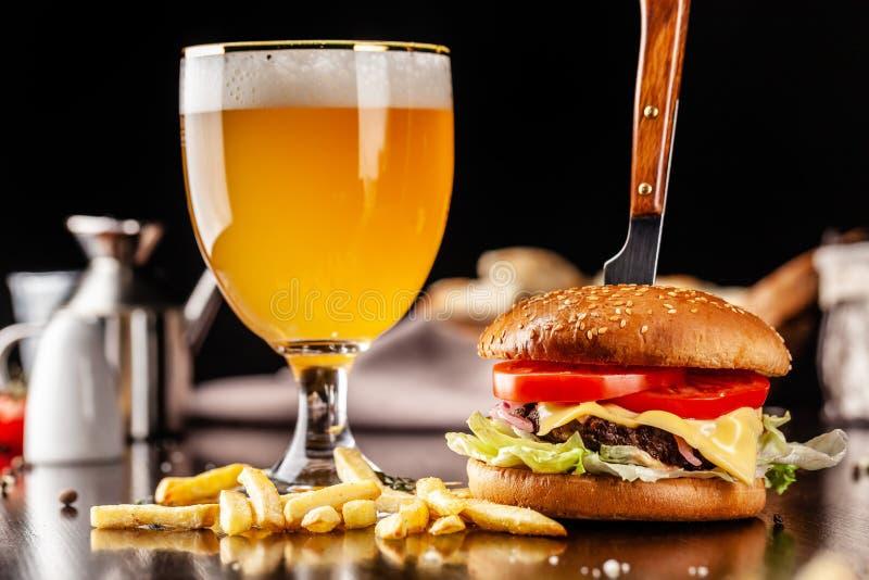 Het concept Italiaanse keuken Italiaanse hamburger met frieten op een houten raad en een glas licht bier met schuim serving stock afbeelding
