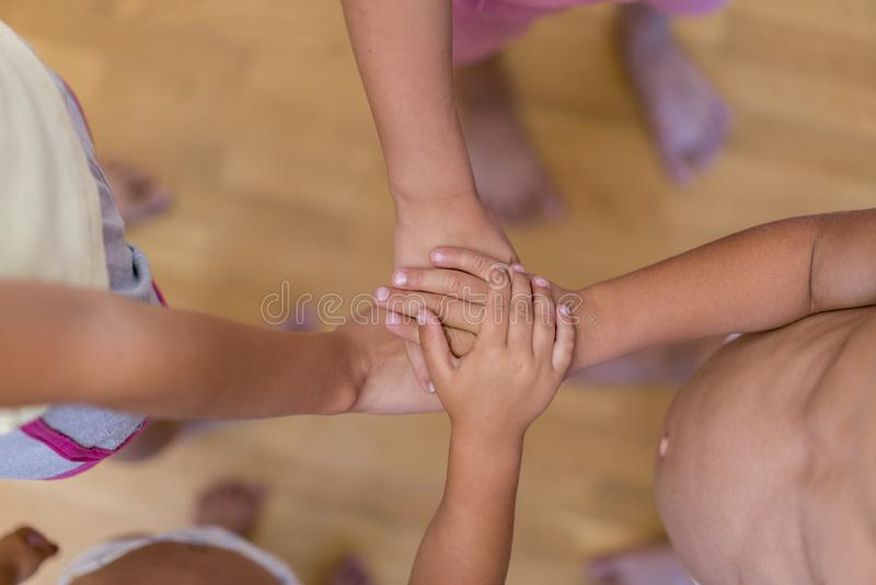 Het concept kindvriendschap en wederzijdse hulp De handen van kinderen aan eenheid worden gestapeld die Gestapelde de handen van  royalty-vrije stock afbeeldingen