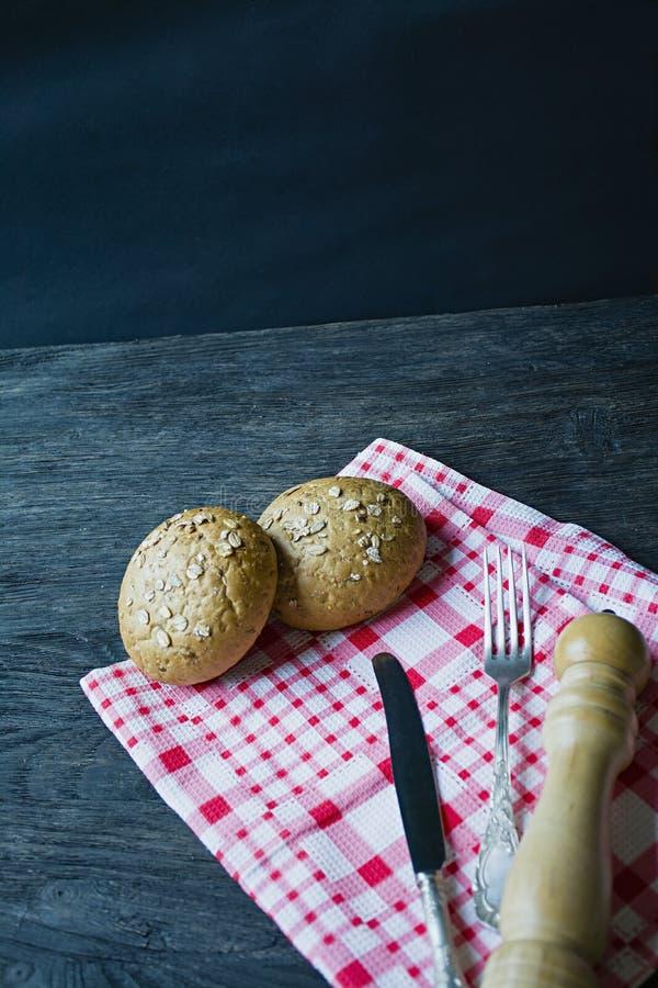 Het concept het koken Vork, voedselmes, geruit servet, broodjes met zonnebloemzaden, houten peperschudbeker bestek stock fotografie