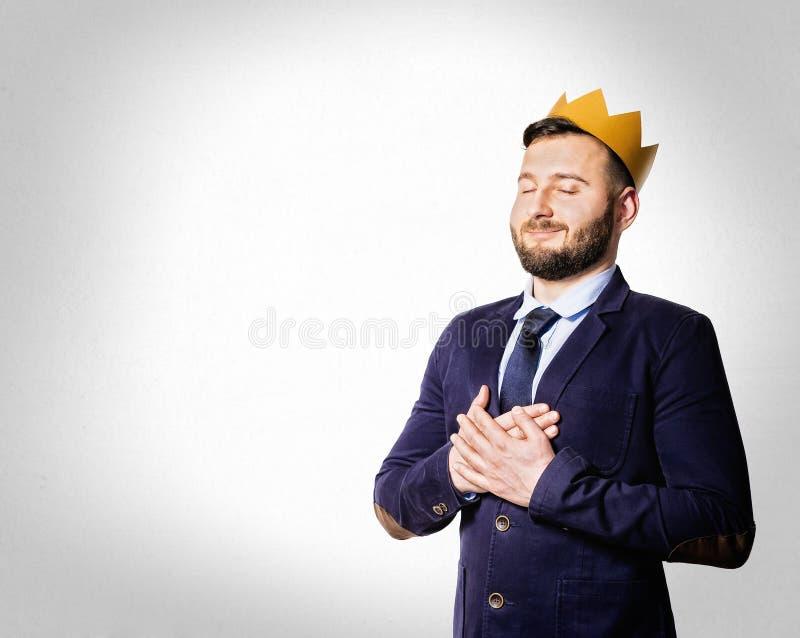 Het concept leiding, voortreffelijkheid Portret van een glimlachende mens met een gouden kroon royalty-vrije stock afbeelding