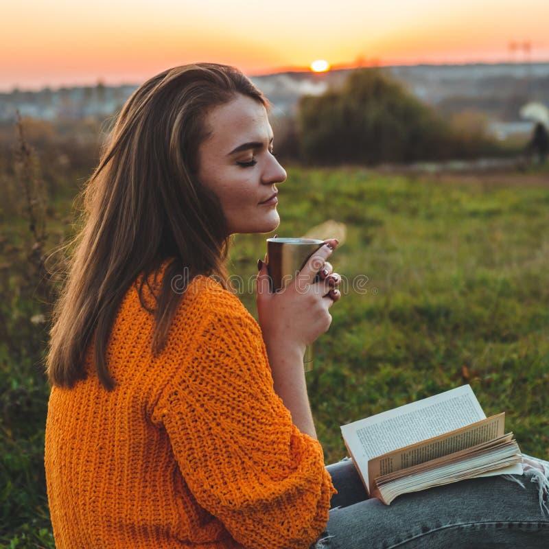 Het concept levensstijl openluchtrecreatie in de herfst Meisje gelezen boeken op plaid met een thermokop De herfst Zonsondergang  stock foto