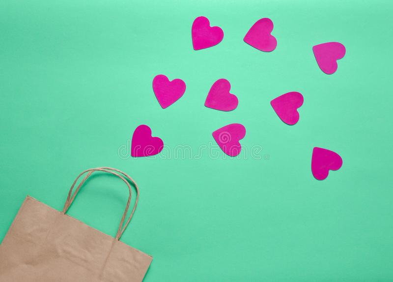 Het concept liefde van het winkelen Een document zak voor het winkelen en veel decoratieve harten op een gekleurde muntachtergron royalty-vrije stock fotografie