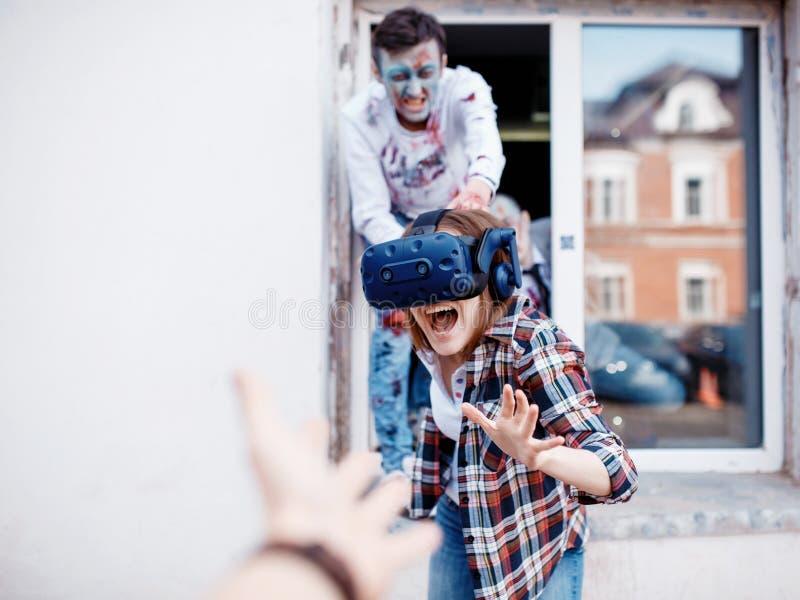 Het concept, het meisje speelt videospelletjes over zombie?n, die virtuele werkelijkheidsglazen dragen Zombiemake-up stock foto