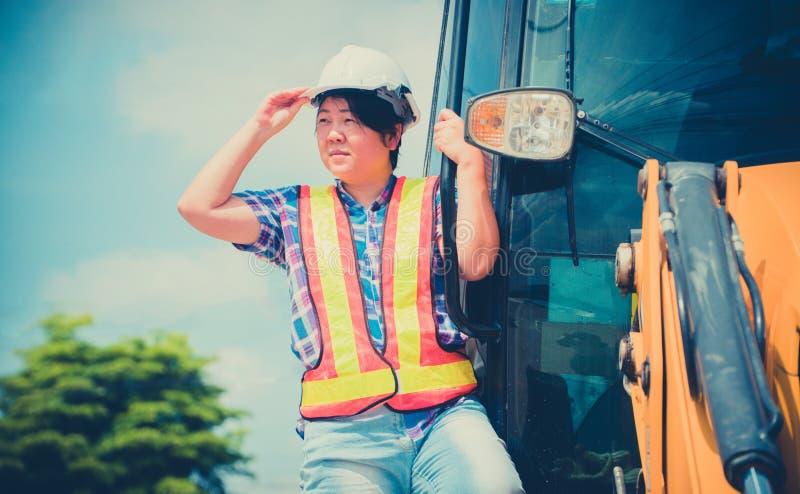 Het concept Moderne vrouwen met gelijke capaciteit voor mannen De Aziatische vrouwelijke ingenieur bevindt zich op backhoe en het stock afbeelding
