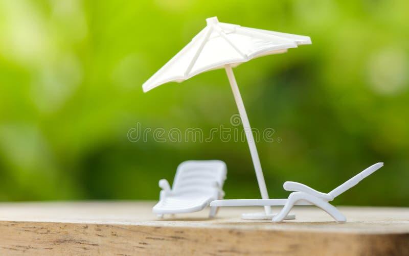Het concept of het plan van de verkoopverzekering ontspant op vakantieparaplu die op bankstoel beschermen voor familie stock afbeelding