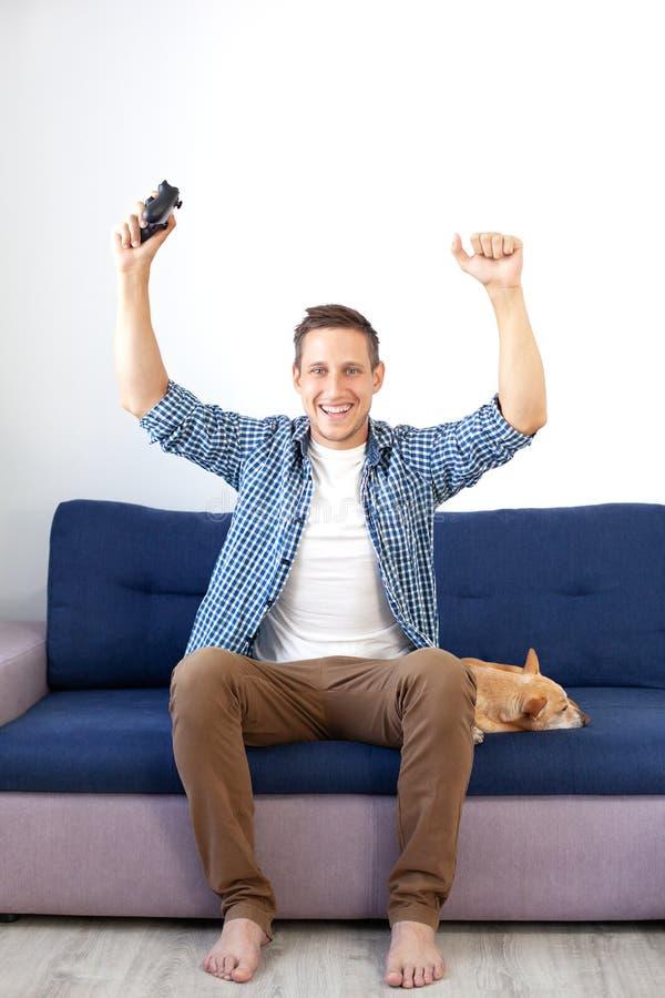 Het concept het spel de kerel speelt thuis een videospelletje met een bedieningshendel met een hond Een glimlachende mens in een  royalty-vrije stock fotografie