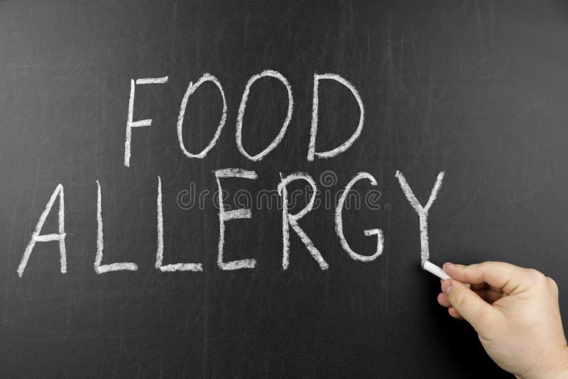 Het concept van het allergievoedsel Hand met krijt die op zwart bord schrijven stock fotografie
