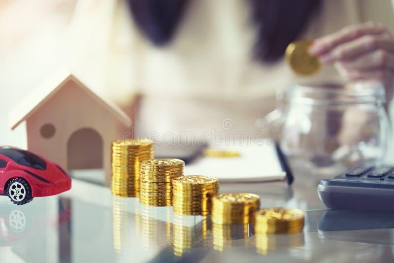 Het concept van het besparingsgeld, Stapel van gloden muntstuk met blokhuis en rode autohypotheek, vrouwenhand zettend muntstukke royalty-vrije stock afbeeldingen