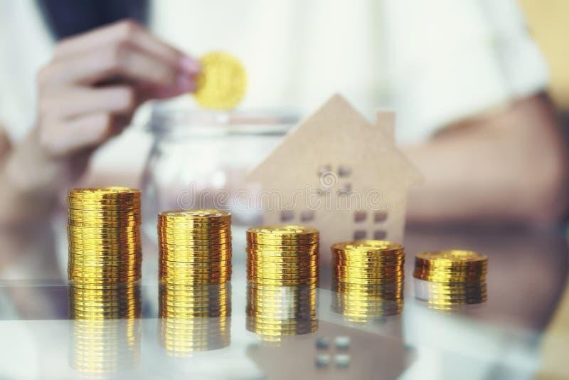 Het concept van het besparingsgeld, Stapel van gloden muntstuk met vrouwenhand zettend muntstukken op de achtergrond van het krui royalty-vrije stock foto