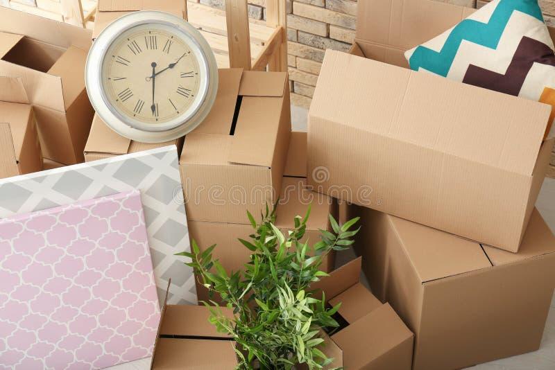 Het concept van het bewegingshuis Kartondozen en bezittingen stock afbeeldingen
