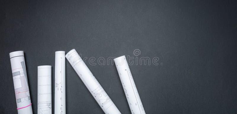Het concept van het bouwproject De broodjes van de architectuurblauwdruk op zwarte achtergrond, exemplaarruimte stock foto's
