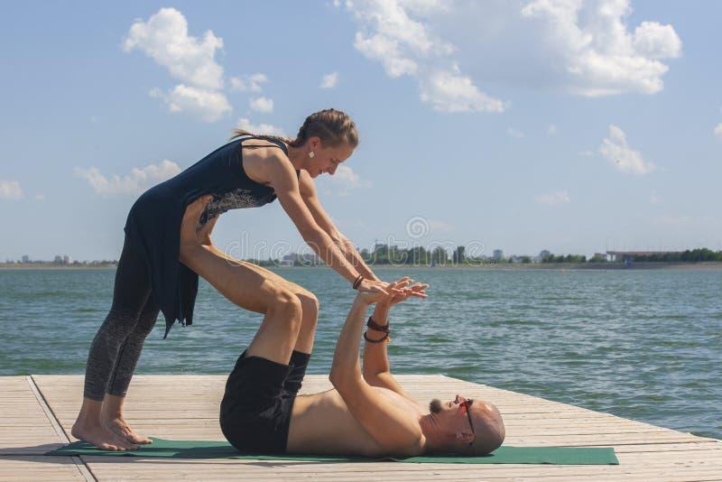 Het concept van de Acroyoga Paaryoga Het paar van jonge sportieve mensen die yogales met partner, de mens en vrouw in yogi uitoef stock foto's