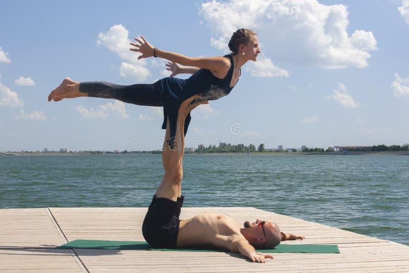 Het concept van de Acroyoga Paaryoga Het paar van jonge sportieve mensen die yogales met partner, de mens en vrouw in yogi uitoef stock afbeeldingen