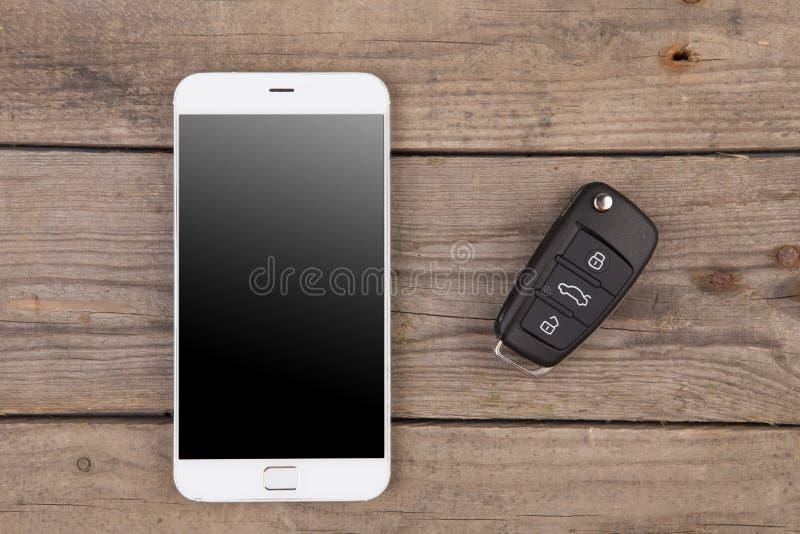 Het concept van de autoveiligheid - sleutel met verre alarmcontrole en smartphone royalty-vrije stock fotografie