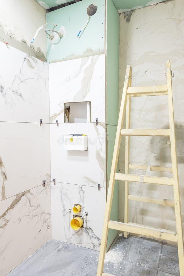 Het concept van de badkamersvernieuwing Marmeren keramische tegels met verbindingsstukken en grijze cementmuren in badkamers die, royalty-vrije stock afbeelding