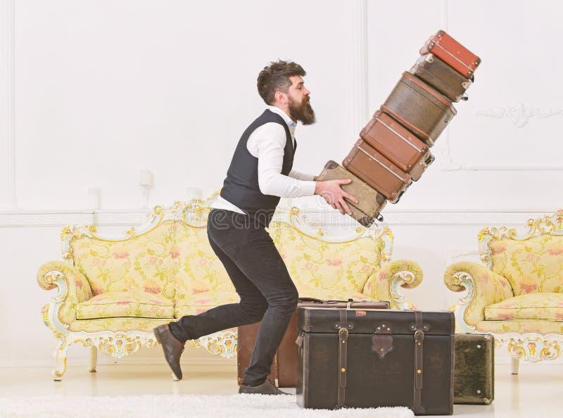 Het concept van de bagageverzekering De portier, butler struikelde toevallig, latend vallen stapel van uitstekende koffers Mens m stock afbeelding