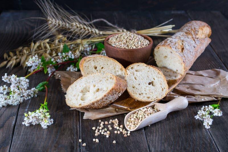 Het concept van de bakkerij Boekweitbrood, Franse baguette en stelen van tarwe, haver, boekweit stock afbeeldingen