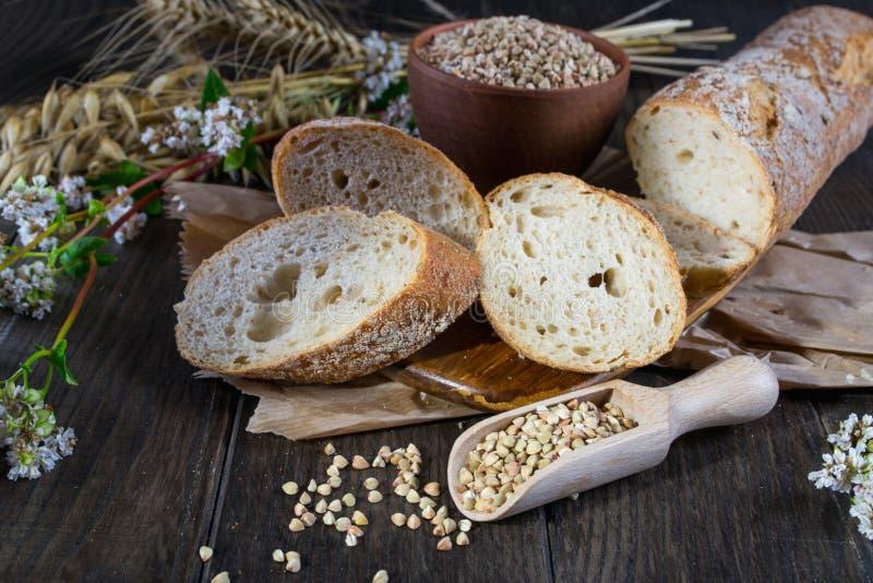 Het concept van de bakkerij Boekweitbrood, Franse baguette en stelen van tarwe, haver, boekweit royalty-vrije stock foto's