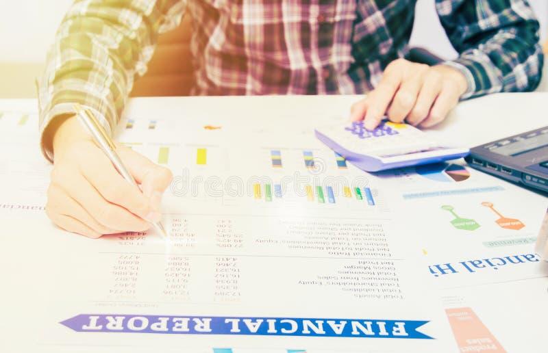 Het concept van de bedrijfsfinanciënboekhouding: de bedrijfsmensenhand calculator gebruiken en het financiënblad die melden analy stock foto's