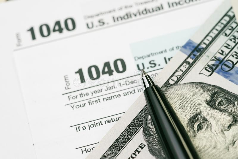 Het concept van de belastingstijd, pen op Amerikaanse dollarrekeningen met het individu van de 1040 V.S. stock afbeelding