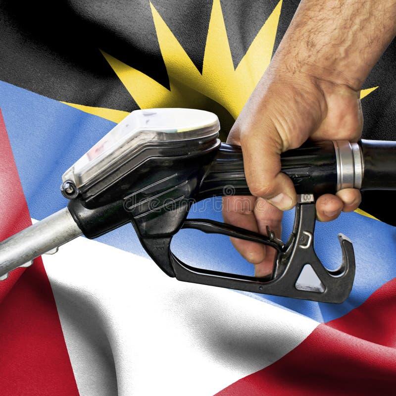 Het concept van de benzineconsumptie - overhandig holdingsslang tegen vlag van Antigua en Barbuda royalty-vrije stock foto's